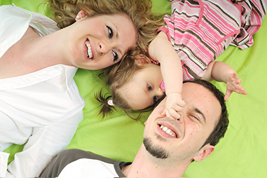 Family with young child lying together and laughing