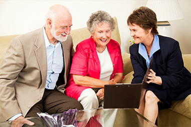 Elderly couple sitting on couch consulting with insurance representative